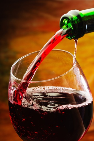 alcohol bottles: Red wine being poured into wine glass Stock Photo