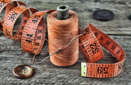 still life of spools of thread on a wooden background photo