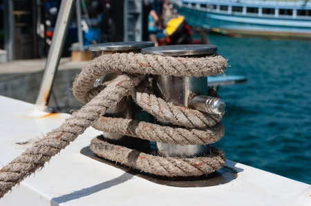 cleat: Knot on a bollard of a boat. Blue sea in a background.