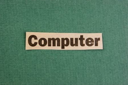 word computer cut from newspaper on green background photo