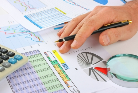 spreadsheets: pen in hand and working paper chart Stock Photo