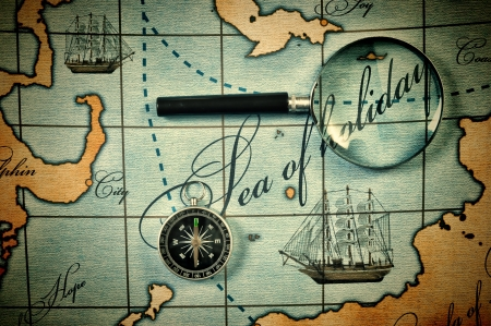 topography: Old magnifier and compass on a stylized map