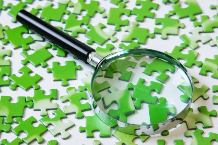 magnifying glass on the green puzzle Stock Photo