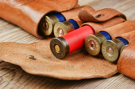 Old hunting cartridges and bandoleer on a wooden table photo