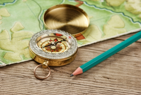 old map and compass on a wooden table photo