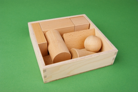 wooden geometric shapes in a box on a green background photo