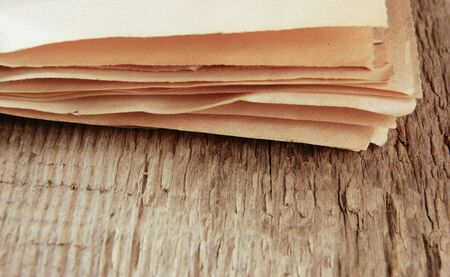 distressed wood: edge of the old newspaper on a wooden background