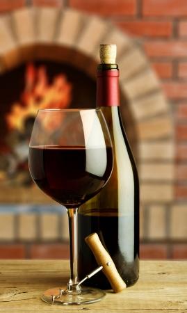 fles en glas rode wijn op de achtergrond van de landelijke open haard