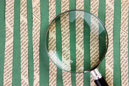 Collage cut from newspaper  and magnifying glass on green background photo