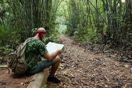Travelling man sitting and looking at the map in the bamboo forest photo