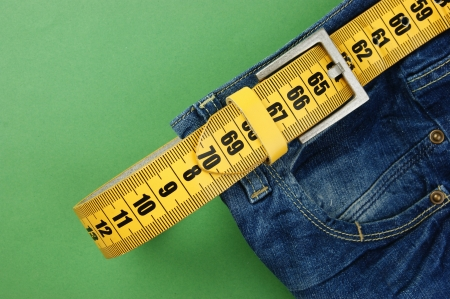 pertinente: jeans con cintur�n de adelgazamiento metros sobre el fondo verde