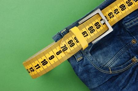 jeans met meter riem afslanken op de groene achtergrond