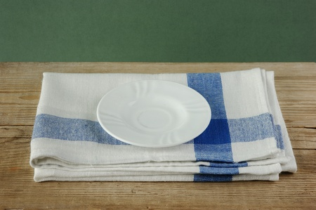 White saucer and dishcloth on old wooden table over green background photo