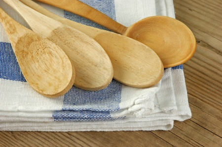 wooden kitchenware  and dishcloth on old wooden table photo