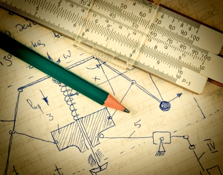 mathematical proof: pencil and a slide rule on the old page with the calculations in mechanics