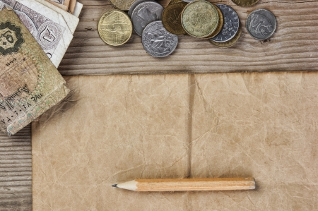 Old notes and coins and pencil on a wooden table Stock Photo - 19491101