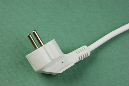 white electrical cable with plug on the green background photo