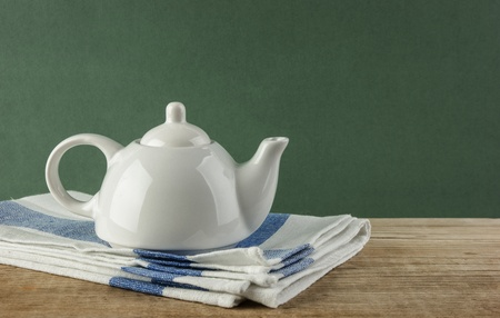 White teapot and dishcloth on old wooden table over green background photo