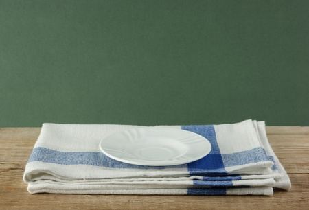 dishcloth: White saucer and dishcloth on old wooden table over green background