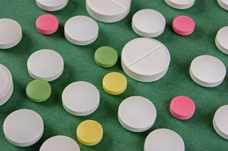 Pills and tablets on a green background photo