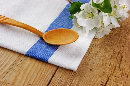 wooden spoon with a flowers and dishcloth on old wooden table photo