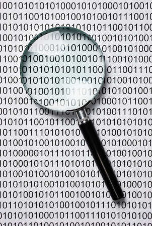 magnifying glass on the background of a binary code photo