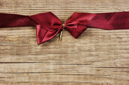 red bow and ribbon on the old wooden background photo