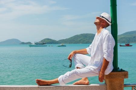Een jonge man in een wit pak zit op de waterkant
