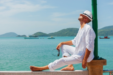 male fashion model: Un hombre joven en un traje blanco se sienta en el paseo mar?mo