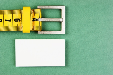 meter belt slimming and blank business card on the green background photo