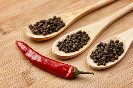 Black and red pepper in wooden spoon on the old board photo