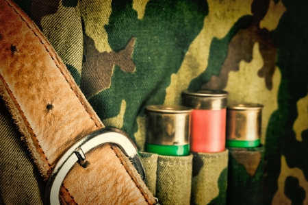 Old hunting cartridges and bandoleer on camouflage background photo