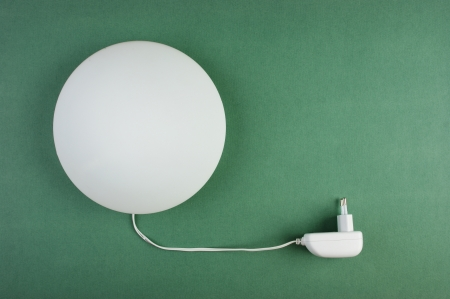 round white lamp with electric plug on a green wall photo