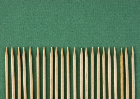 wooden toothpicks in paling shape on the green background photo