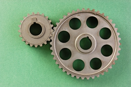 Two gears  on a green background photo