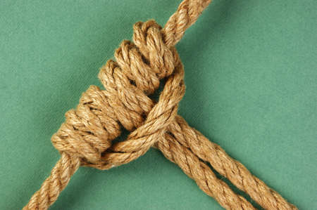string together: Rope with marine knot  on the green background Stock Photo