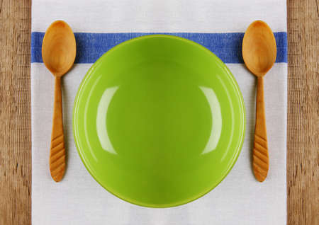 wooden spoon with a plate on the table cloth on an old wooden table photo