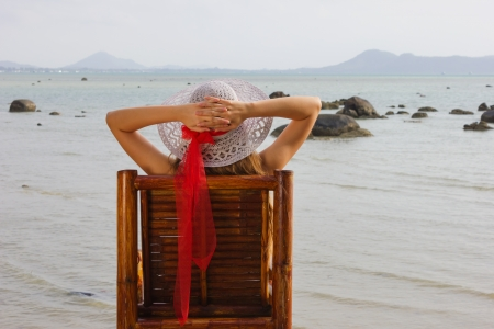 young girl sitting on a chair and looks at the sea photo