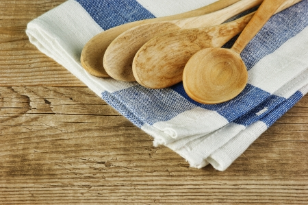 wooden spoon and dishcloth on old wooden table photo