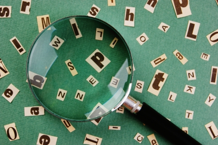 letters cut from newspaper and magnifying glass on green background photo