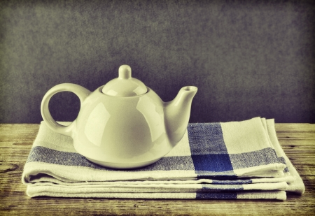 dishcloth: White teapot and dishcloth on old wooden table over green background