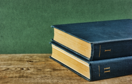 Old books on a wooden shelf against a green wall photo