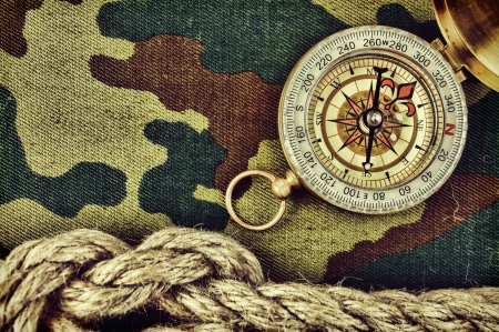 army background: Compass and rope on a camouflage background
