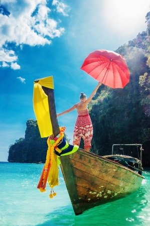 longtail: young girl standing in a wooden boat with a red umbrella in the Gulf of Phi Phi Don Thailand
