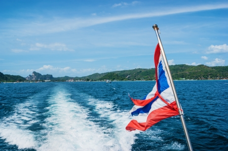 The national flag of thailand on the stern of the boat and the view of the wake photo