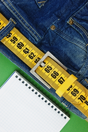 jeans with meter belt slimming and notebook on the green background photo
