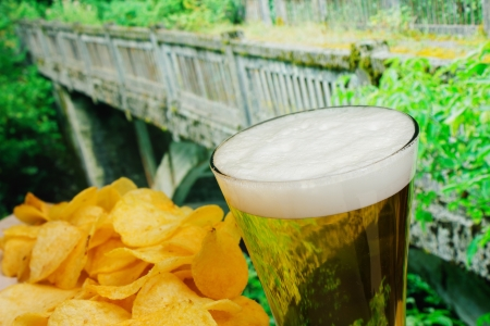 glass of beer and potato chips in a landscape photo
