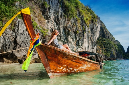 young girl  in a wooden boat  in the Gulf of Phi Phi Don Thailand photo