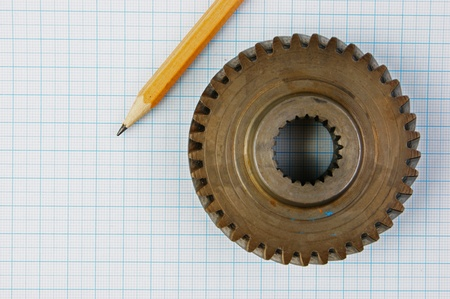 Gear and pencil on graph paper photo
