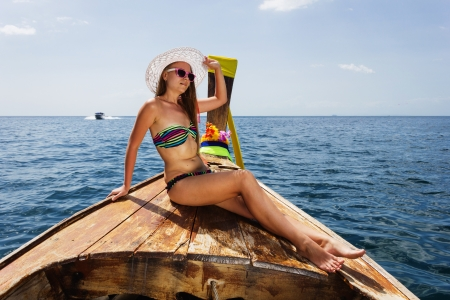 young girl in bikini sitting on Thai Longtail boat photo